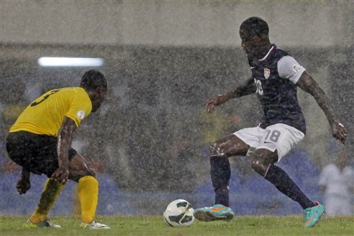 Under pouring rain, Eddie Johnson (R) challenges Antigua and Barbuda's Zaine Sebastian Francis-Angol. (AP)