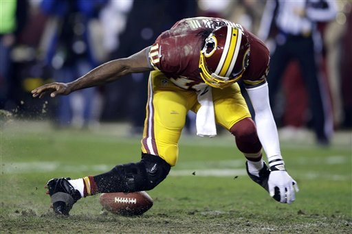 Robert Griffin III twists his knees as he reaches for the loose ball in a loss to Seattle. (AP)