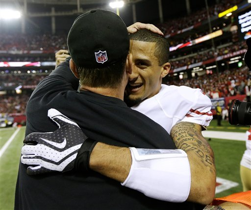 Colin Kaepernick hugs coach Jim Harbaugh following the Niners' victory over the Falcons. (AP)