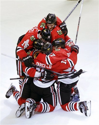 Daniel Carcillo is mobbed after scoring game-winning goal against the Avs. (AP Photo)