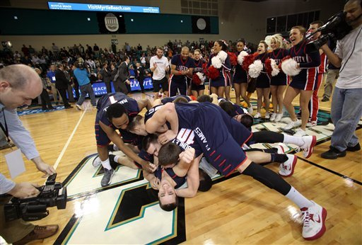 Liberty players celebrate at mid-court after defeating Charleston Southern 87-76 in the Big South championship. (AP)