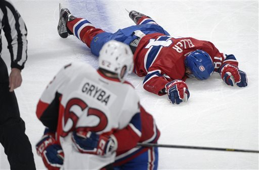 The Habs' Lars Eller lies injured on the ice following a hit by Sens' Eric Gryba (AP Photo/The Canadian Press).