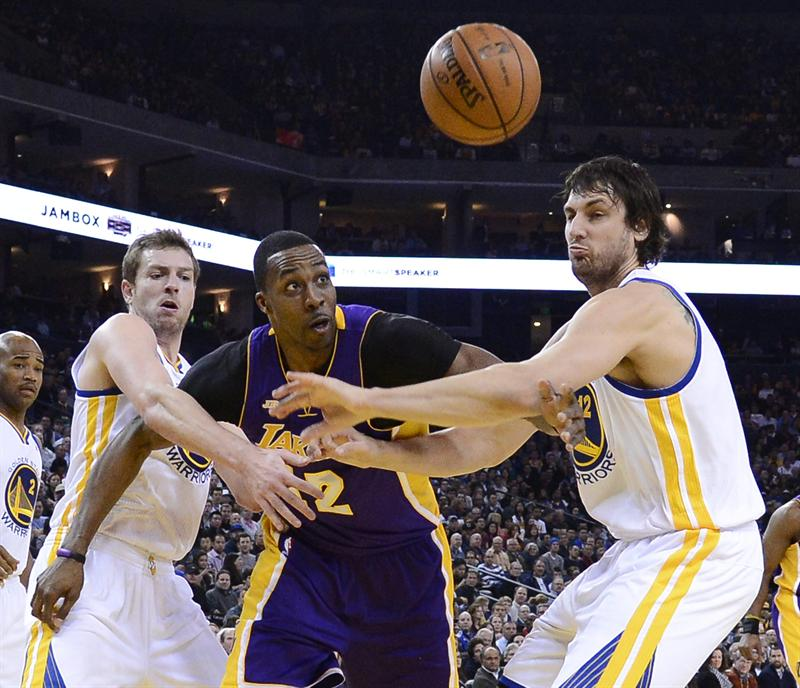Dwight Howard didn't appreciate some of the rough treatment he got from David Lee (L). (EFE)