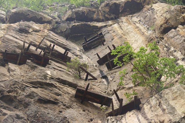 Những chiếc quan tài gỗ được làm từ thân cây đóng vào vách đá bằng 2-3 thanh gỗ lớn.