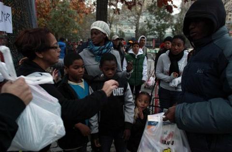 Dòng người xếp hàng ở New York hôm qua chờ nhận thức ăn, nước và các nhu yếu phẩm sau bão. Ảnh: AFP