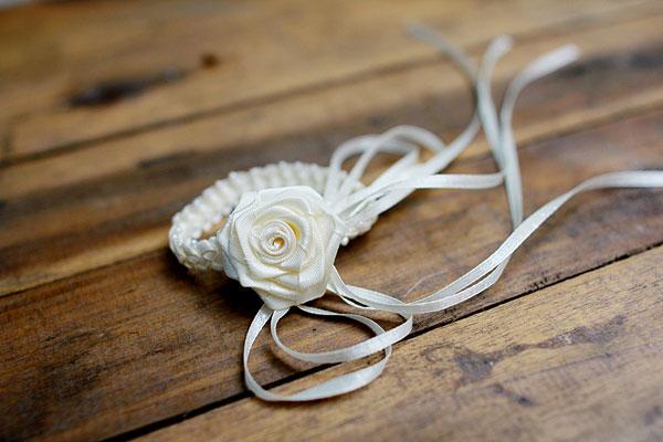 Chiếc vòng tay được kết từ ribbon, đính hạt viền tinh tế. Bông hoa là điểm nhấn nhẹ nhàng. Với màu trắng kem truyền thống, chiếc vòng tay thích hợp cho cả cô dâu và phù dâu.