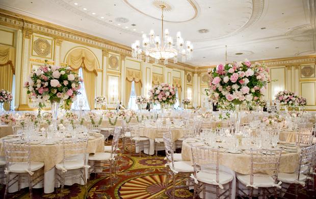 Phòng tiệc có tông màu trang trí cố định làm vàng ngà, do đó nhà tổ chức tiệc cưới đã sử dụng những bình hoa lớn để thu hút sự chú ý khách mời vào bàn tiệc.