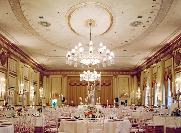 Phòng tiệc sang trọng với những chiếc đèn chùm lớn, không gian ngập tràn sắc màu vàng đồng nhẹ nhàng.
