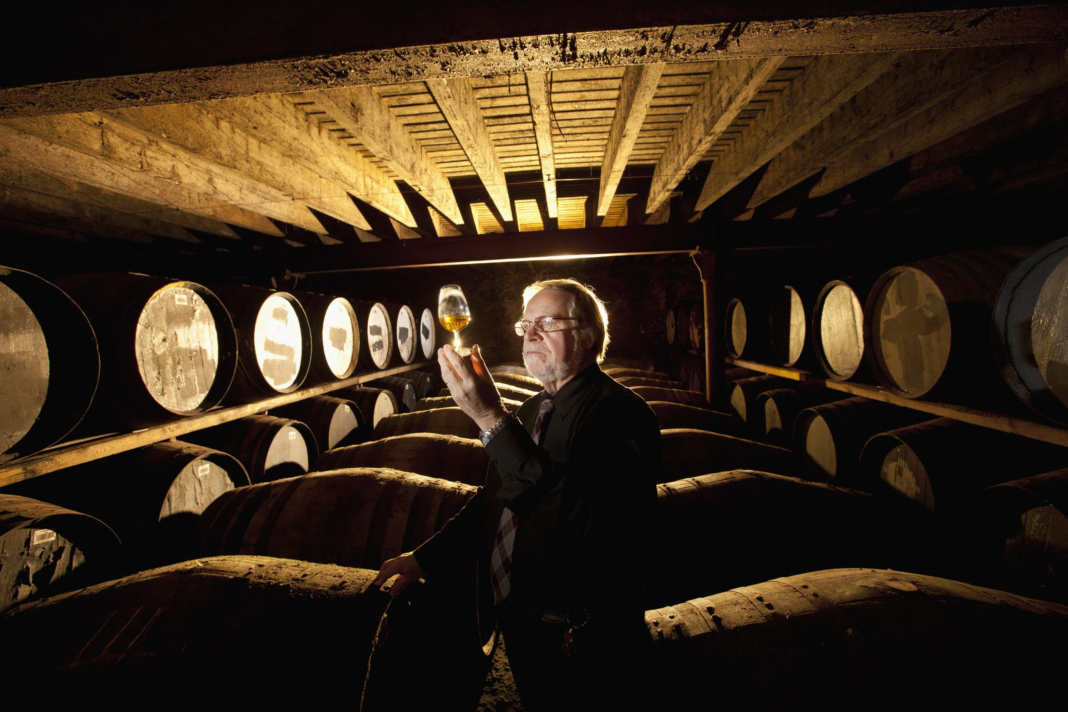 Worker testing whisky in distillery
