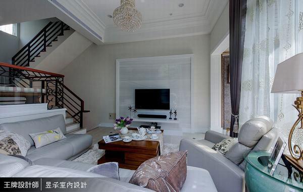 在挑高的客廳空間,喜歡溫馨簡約的屋主不喜歡過於華麗的美式古典,特別以純淨優雅的冰晶白玉大理石材作為電視主牆,搭配簡潔古典線板框,呈現出空間的大氣與美感。