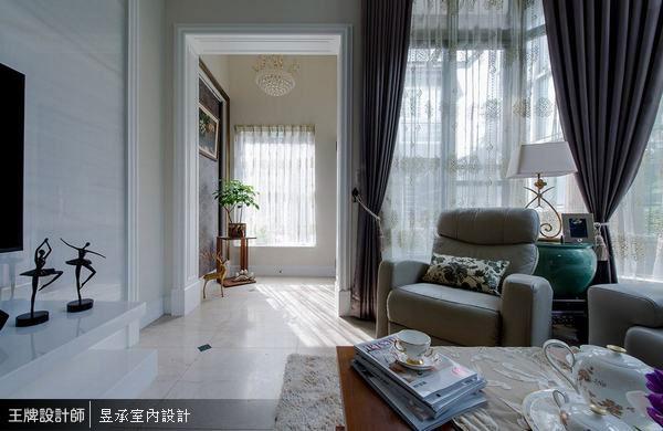 昱承室內設計利用原始別墅的採光優勢,在採光最美的進門處,以金色畫框、深紫色壁紙作為玄關視覺端景,穿過古典造型的方型拱門,帶出整個空間的美式溫馨情境。