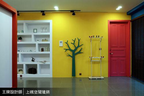 造型樹與小鳥棲架置於亮黃色閱讀區,搭配紅色門扉的活潑設計,彷彿故事書場景的真實呈現。