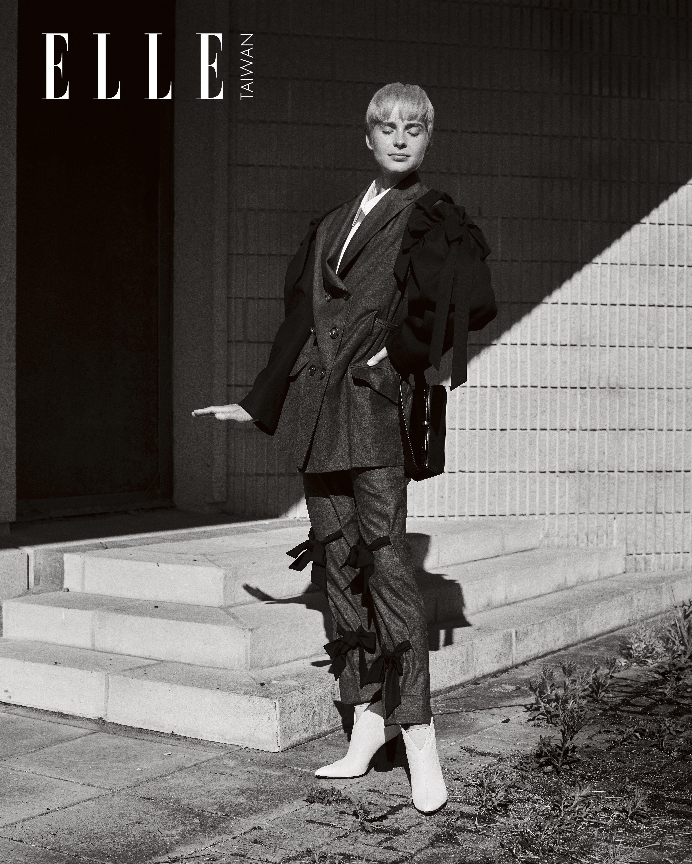 灰黑色西裝外套、白色襯衫、灰黑色造型系帶西褲(ALL BY SIMONE ROCHA);白色靴子(MAGDA BUTRYM);黑色包包(VICTORIA BECKHAM)。