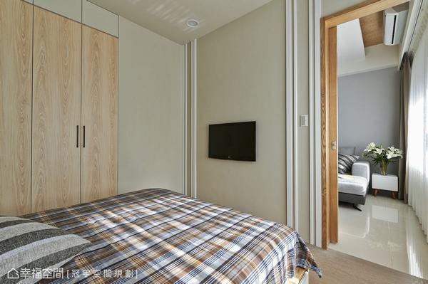 回應客廳空間的灰色優雅,灰綠色的牆面選色更貼近自然,設計者透過白色的線條貼飾,俐落畫出對稱安定的電視牆。