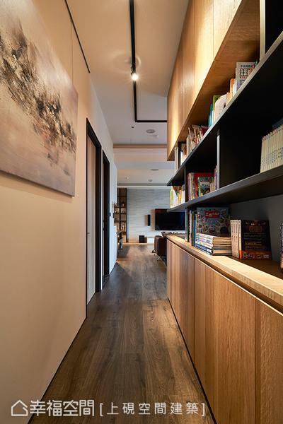 帶有書香氣息的櫃體,與吊掛藝術品的壁面相輝映,並以投射燈凸顯質感,營造出人文書店般的氛圍。