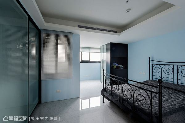 長輩房以天藍色調舒緩氛圍,而曲線造型的黑鐵床架則延續工業風韻味,至於床尾牆櫃選用玻璃門片可減緩牆阻感。