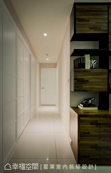 廊道左側規劃有獨立的衣帽間,右側則帶入不等比例的書櫃設計,增添視覺上的趣味與變化。