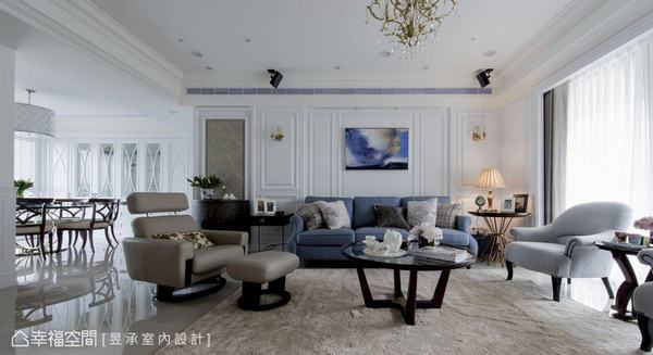 沙發背牆,以層次分明的線板及古典壁板傳遞美式風的經典語彙,透過落地窗引進美好採光,純淨白牆搭配屋主特別挑選的藍色美式沙發及畫作,呈現出明亮紓壓的氛圍。