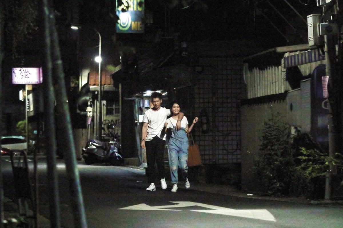 喝醉的簡宏霖(左)在女友攙扶之下步出KTV,女友看他喝醉還樂不可支。