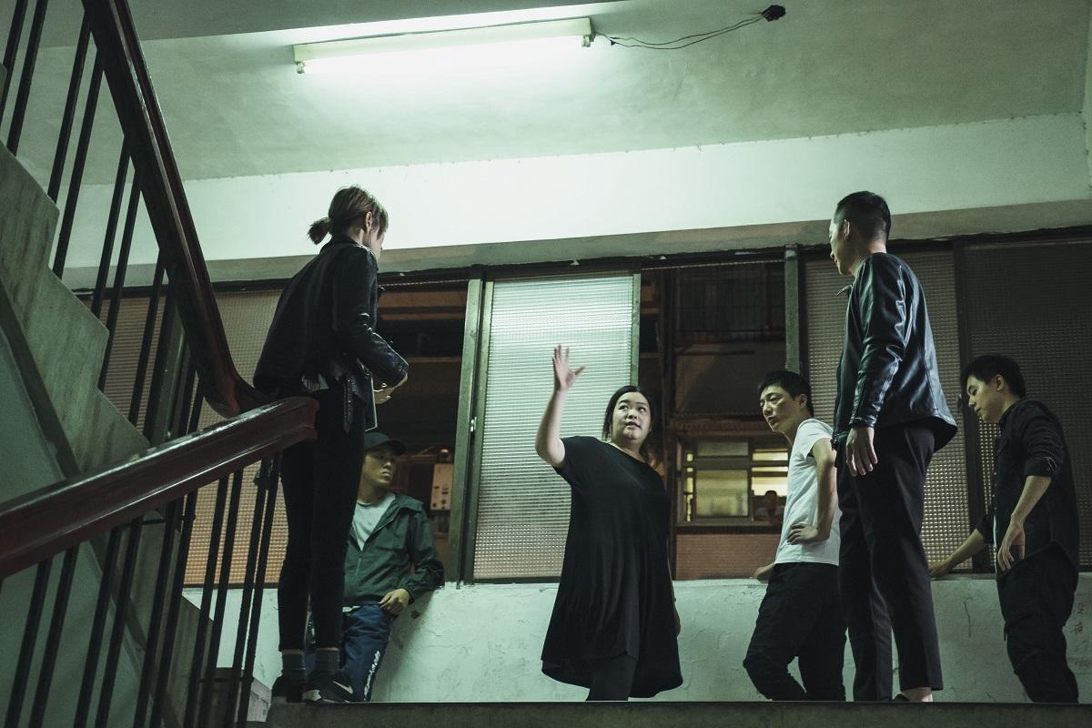 首集登場的追逐跳樓戲,謝庭菡(中)仔細向飾演亡命黑道的藍葦華(右三)說明如何拍攝。(公視提供)