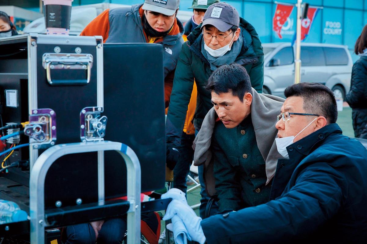 梁宇皙(右一)、男主角鄭雨盛(右二)在《鋼鐵雨》拍攝現場與工作人員檢視畫面。(NEW提供)