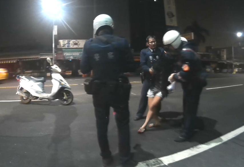 酒醉女一度要衝向馬路,警方用強制力將她上銬,並保護管束。(警方提供)