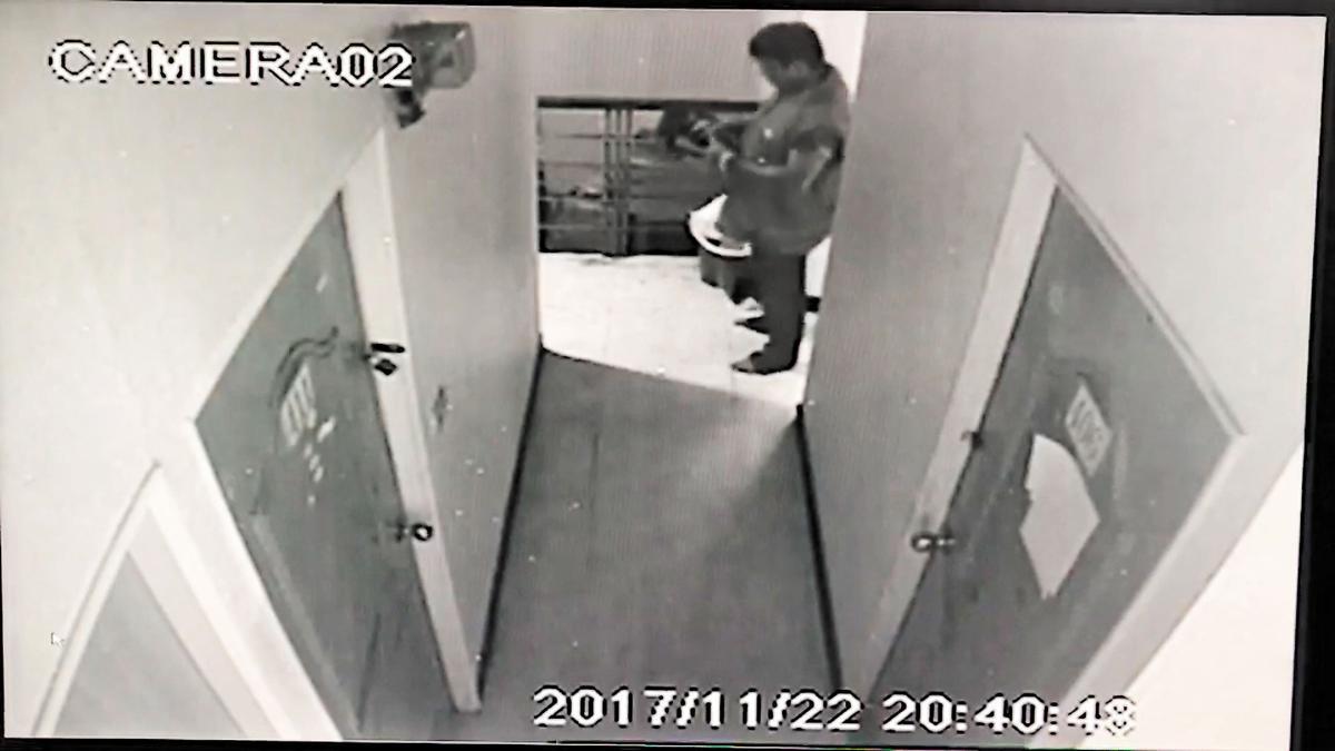 李國輝22日晚間提著便當假裝要找胡姓同鄉,卻到樓梯間點火害命。(翻攝畫面)