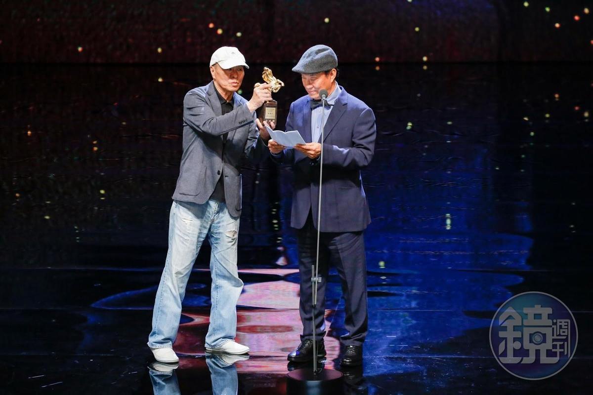 廖慶松獲頒金馬獎特別貢獻獎,從頒獎人侯孝賢手上接過獎座。