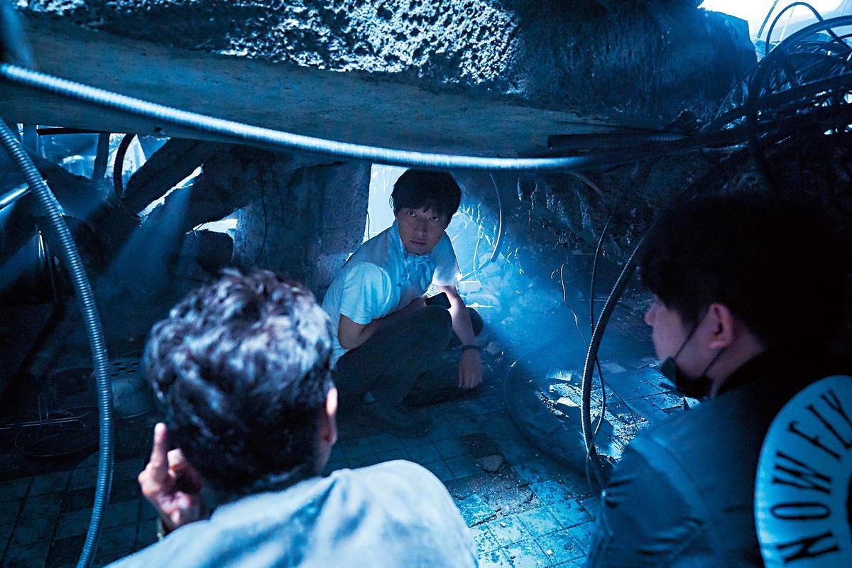 金秉祐(中)精心搭建爆炸後的DMZ地下碉堡,指導劇組如何拍攝才能呈現緊湊節奏。(華聯國際提供)