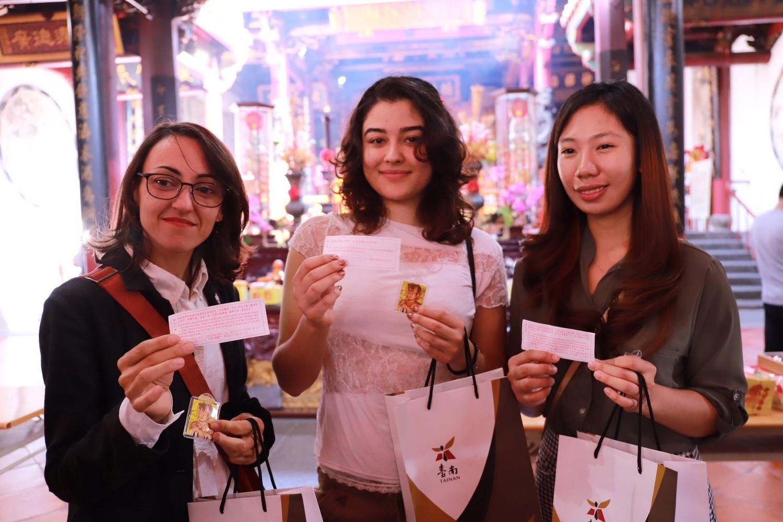 法國籍Christelle, 哥倫比亞Mara 以及菲律賓籍Bae興奮地拿著雙語籤詩合照圖:台南市政府第二官方語言辦公室/提供