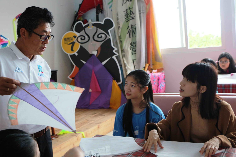 連俞涵和老梅國小學童在風藝術營區風箏高手李青田(左白衣者)協助下,動手合組石門特色的「微風型風箏」和「室內風箏」。圖:新北市民政局提供
