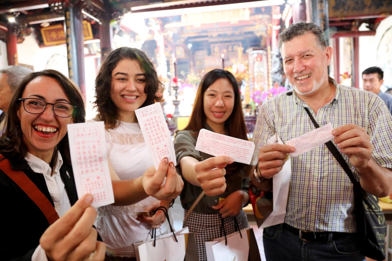 外國旅客抽籤體驗在地宗教文化樂趣。圖:台南市政府第二官方語言辦公室/提供