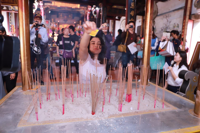哥倫比亞籍Mara拿著平安符繞香爐祈求平安圖:台南市政府第二官方語言辦公室/提供