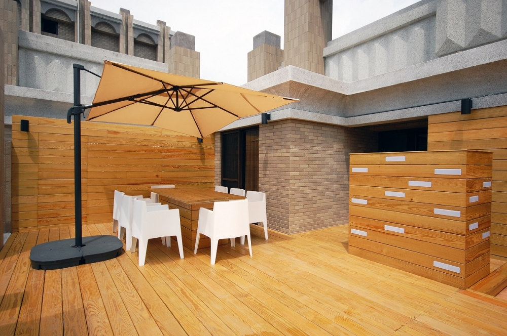 頂樓露台使用南方松打造休閒空間,適度墊高亦具隔熱效果。圖片提供/Ai建築及室內設計