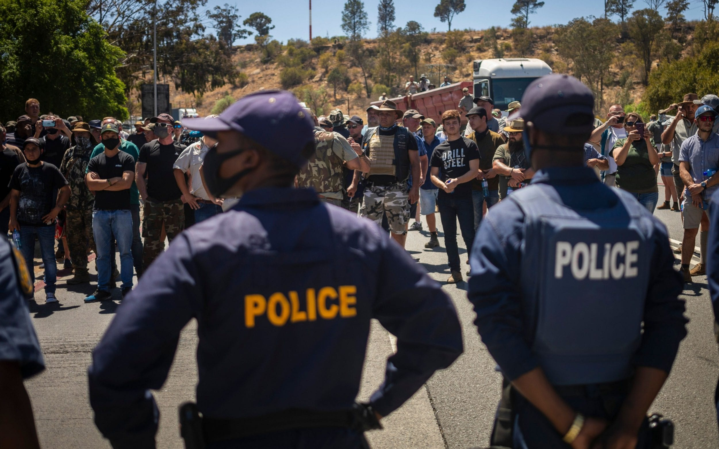 South African white farmers and rival black protesters face off outside court hearing over farm murder case