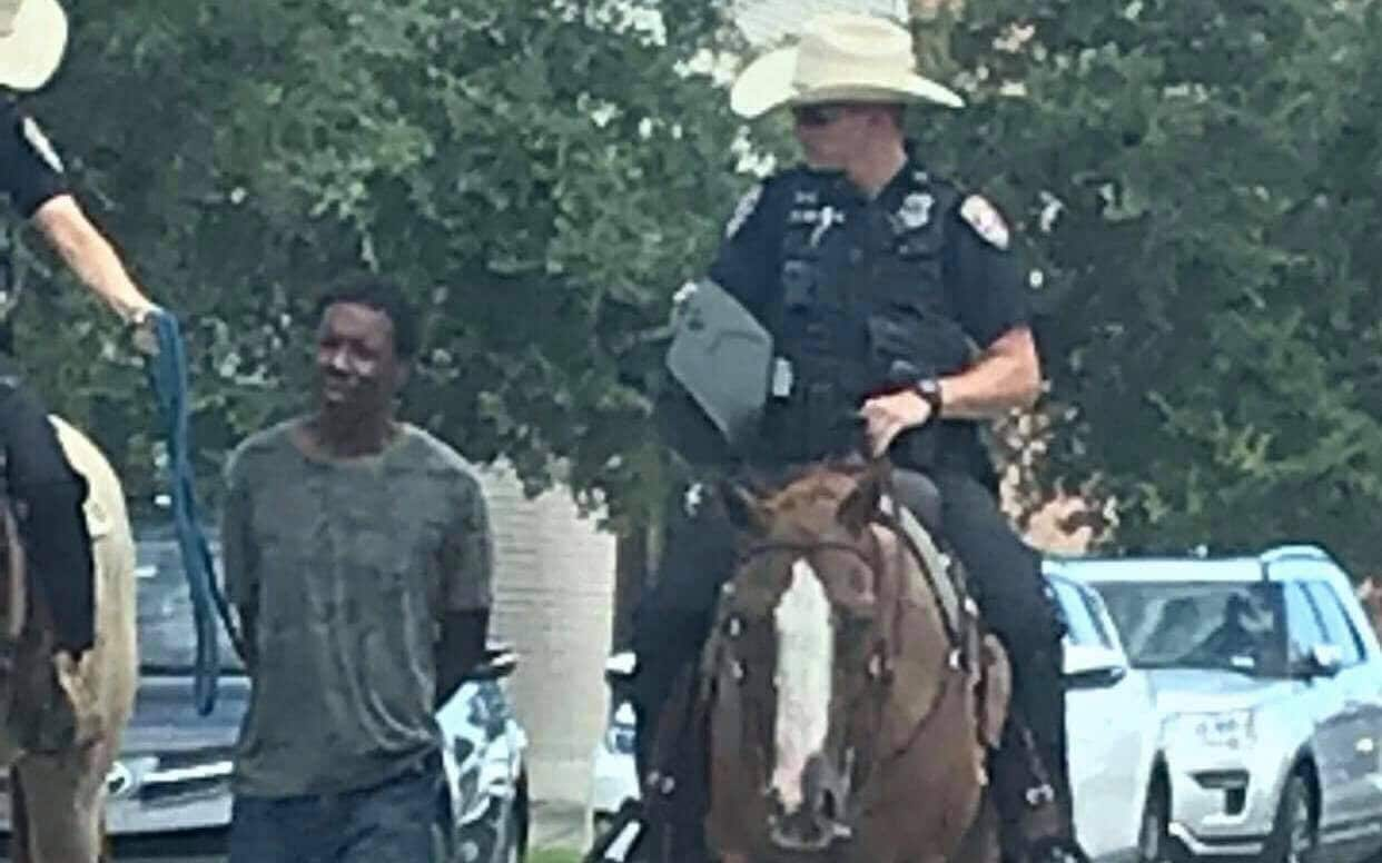 Texas police condemned after officers on horseback lead black suspect by rope
