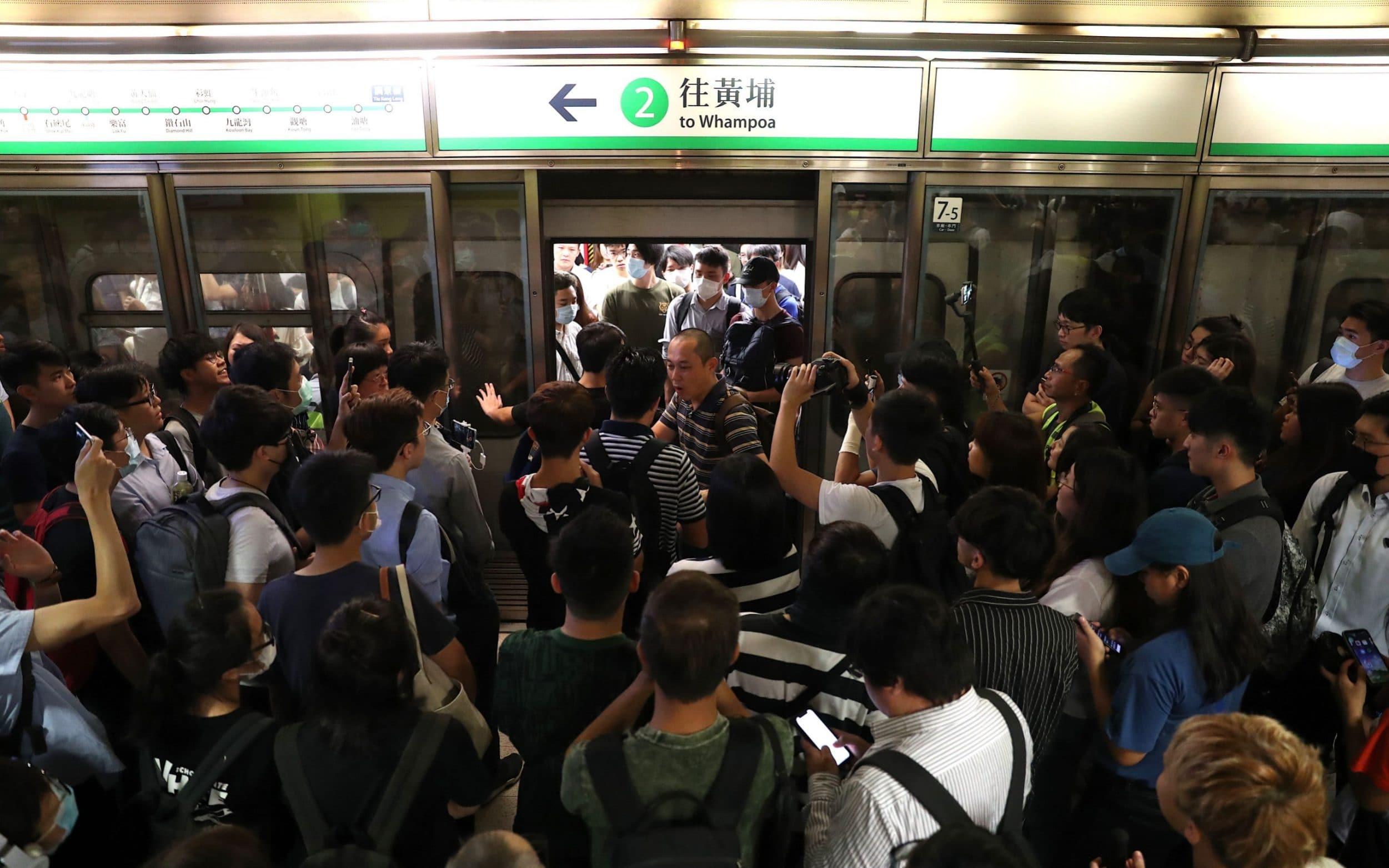 Hong Kong protesters block train doors from closing to disrupt subway services