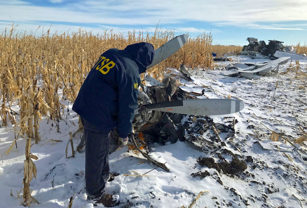 An NTSB investigator examines the wreckage of a Pilatus PC-12 airplane at Chamberlain Municipal Airport in South Dakota