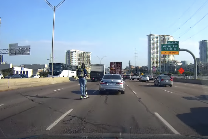 Dashcam captures man riding  a Lime scooter on the highway during rush hour