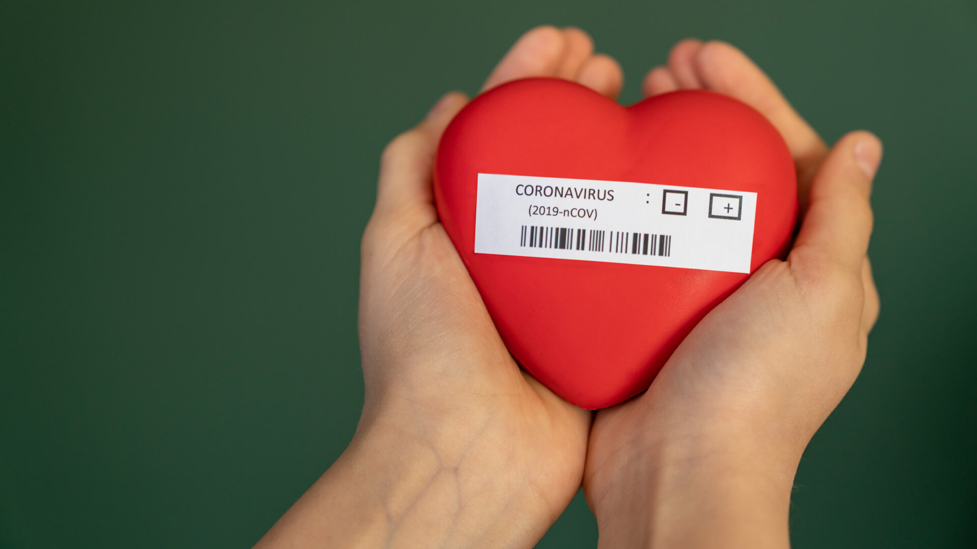 girl holding coronavirus written heart shape in her hand.