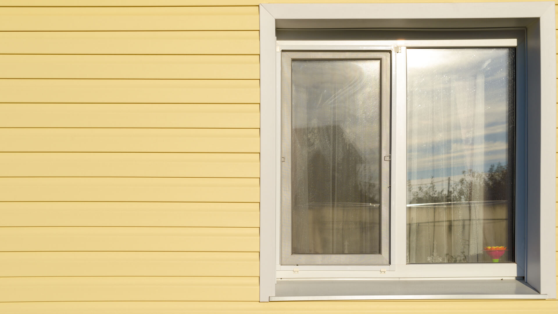 white plastic window on the wall lined with yellow siding.