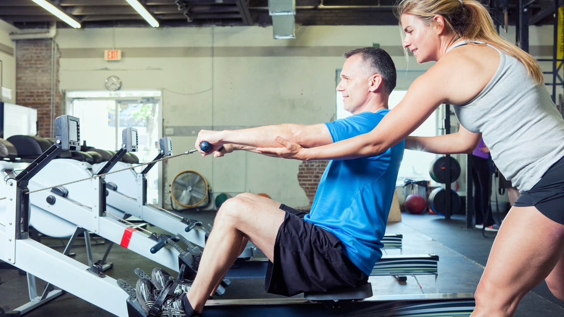 Personal trainer working with her client at a gym.