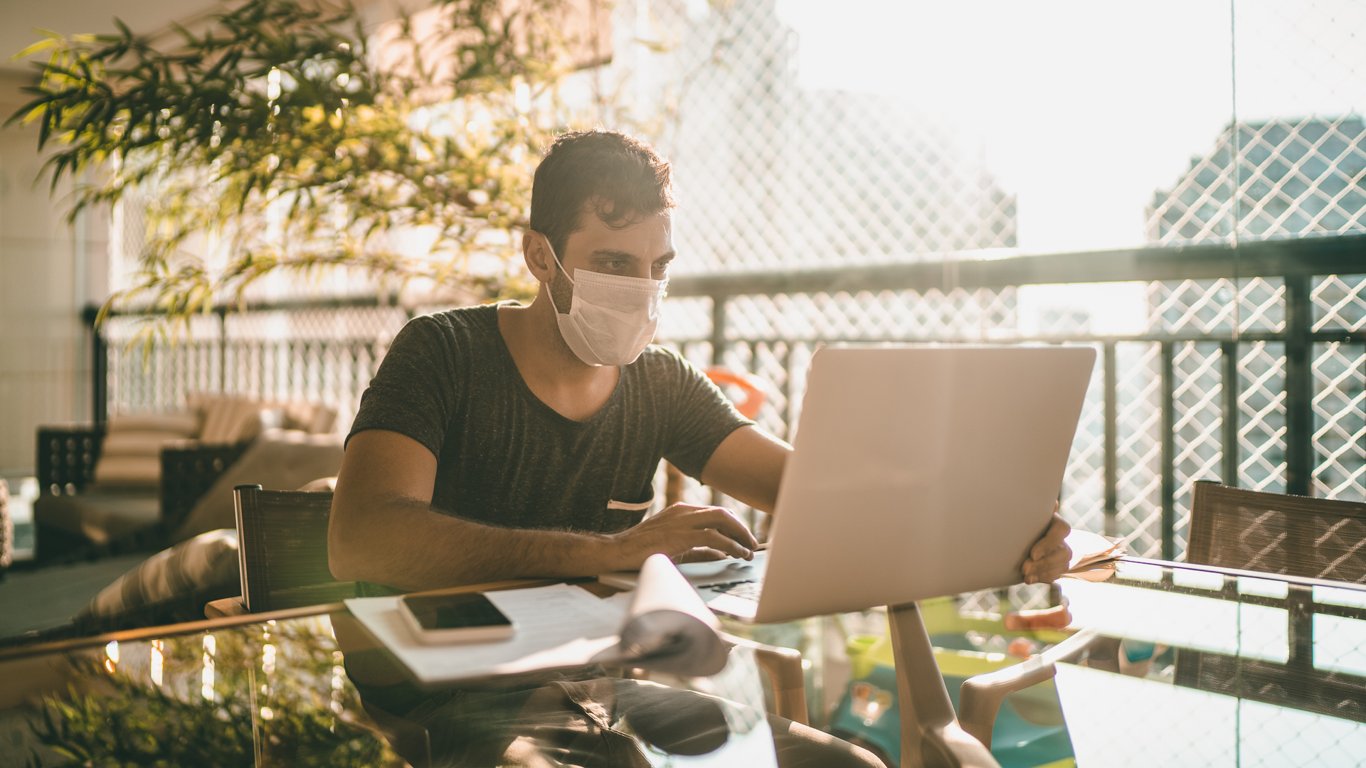guy with face mask sending payment laptop