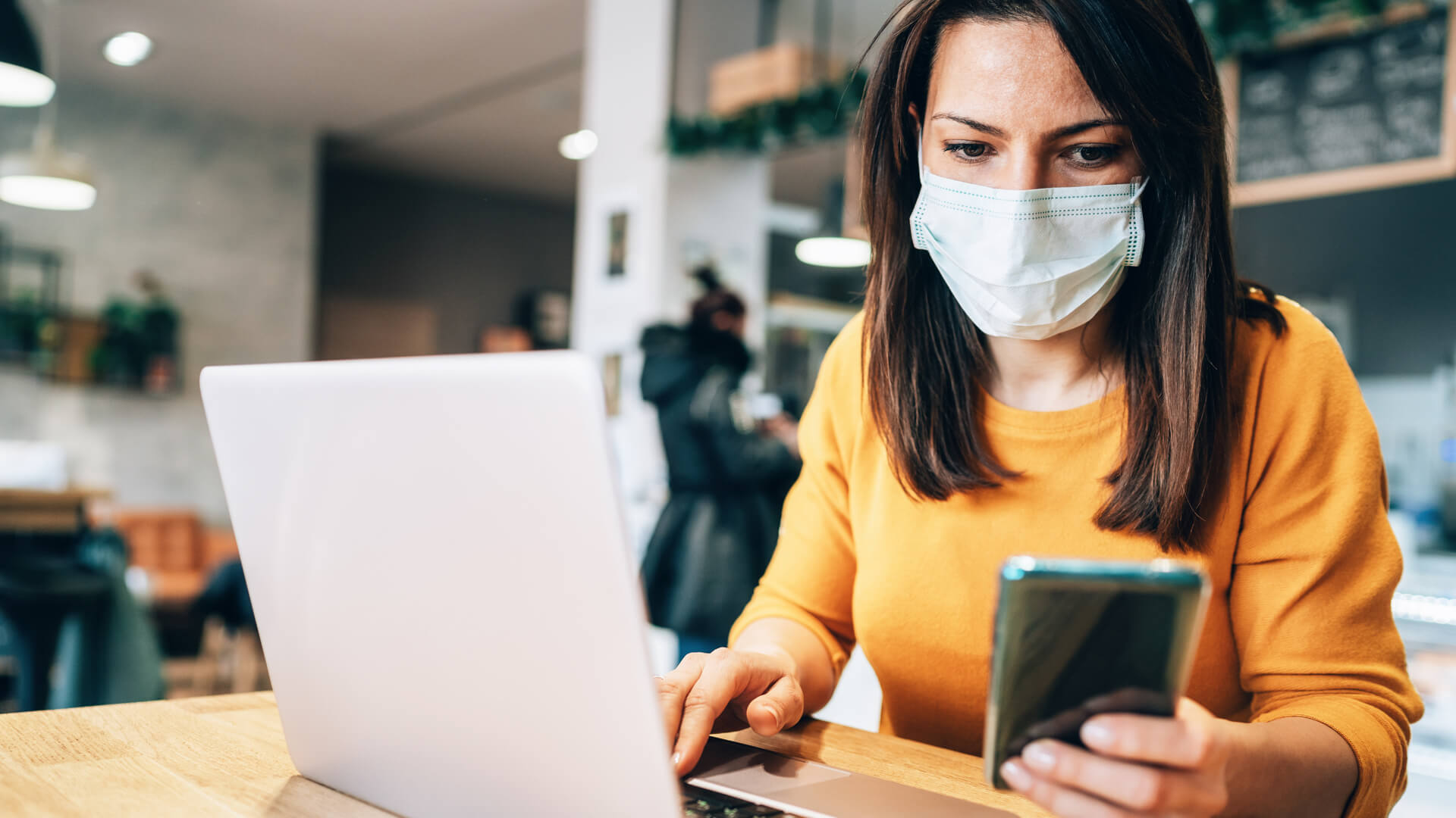 Portrait of young woman using laptop at cafe wearing  face protective mask to prevent infectious diseases.