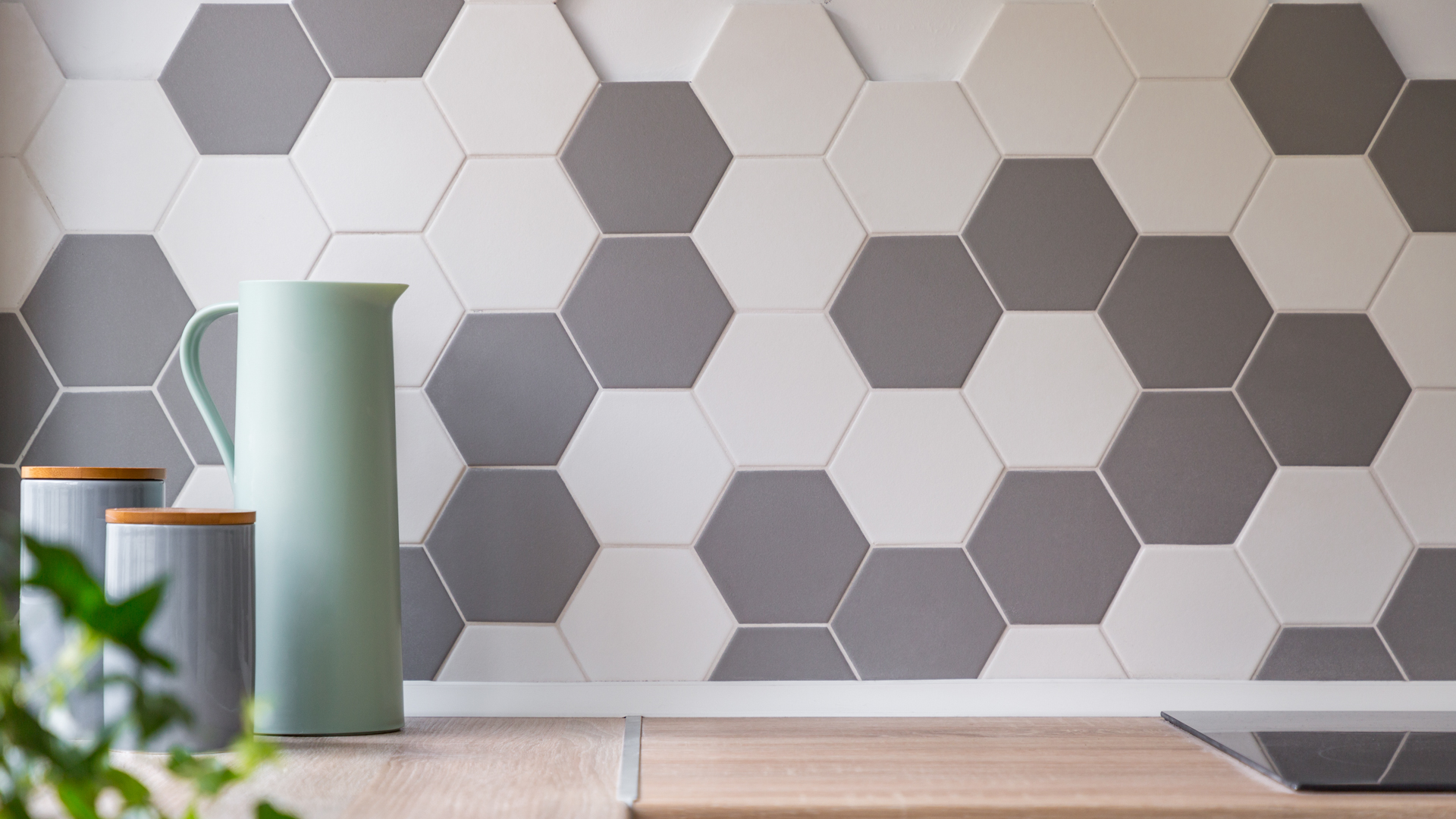 Kitchen with honeycomb wall tiles and wooden worktop.
