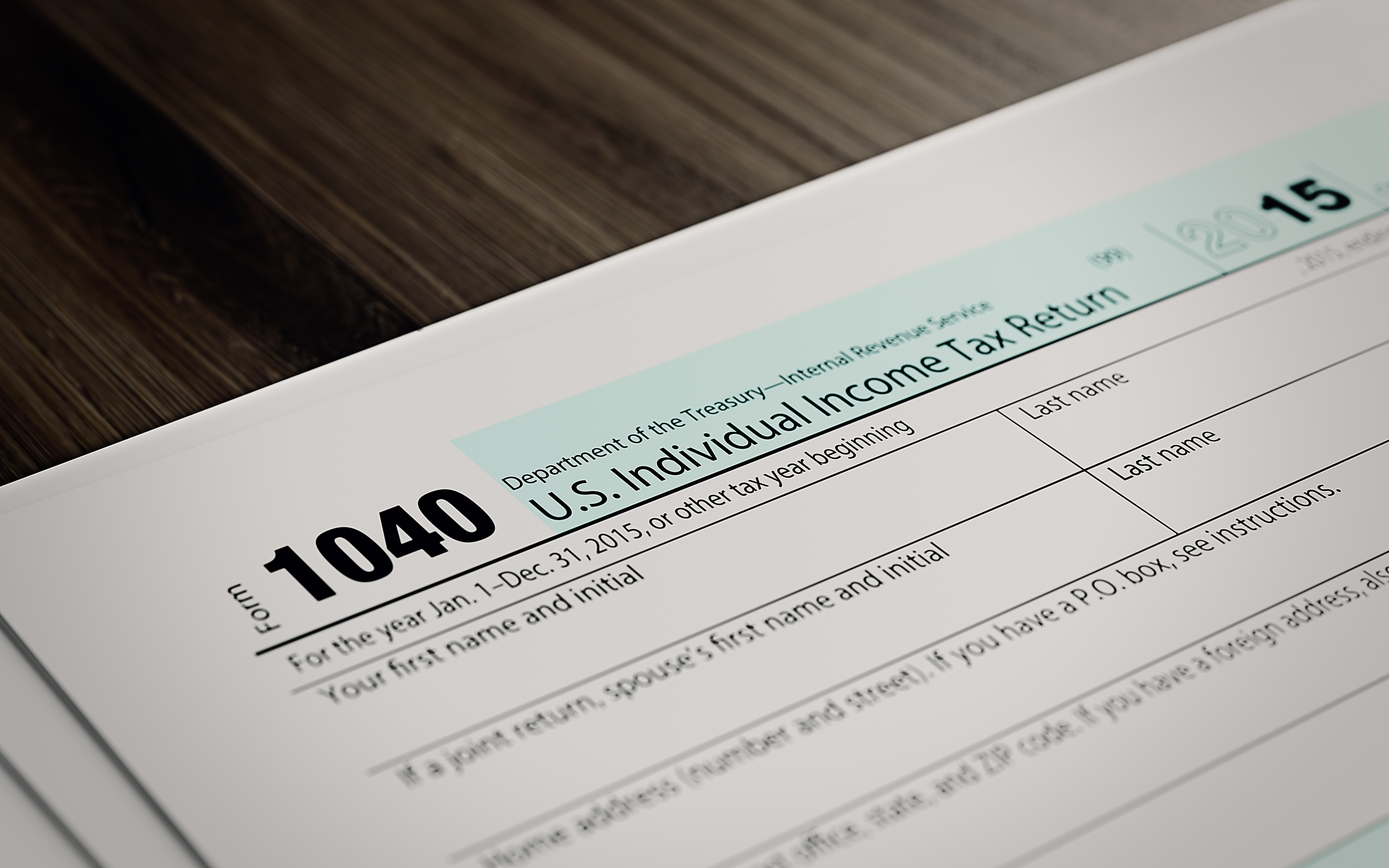 Tax refund form on brown wood surface. Horizontal composition with copy space and selective focus.