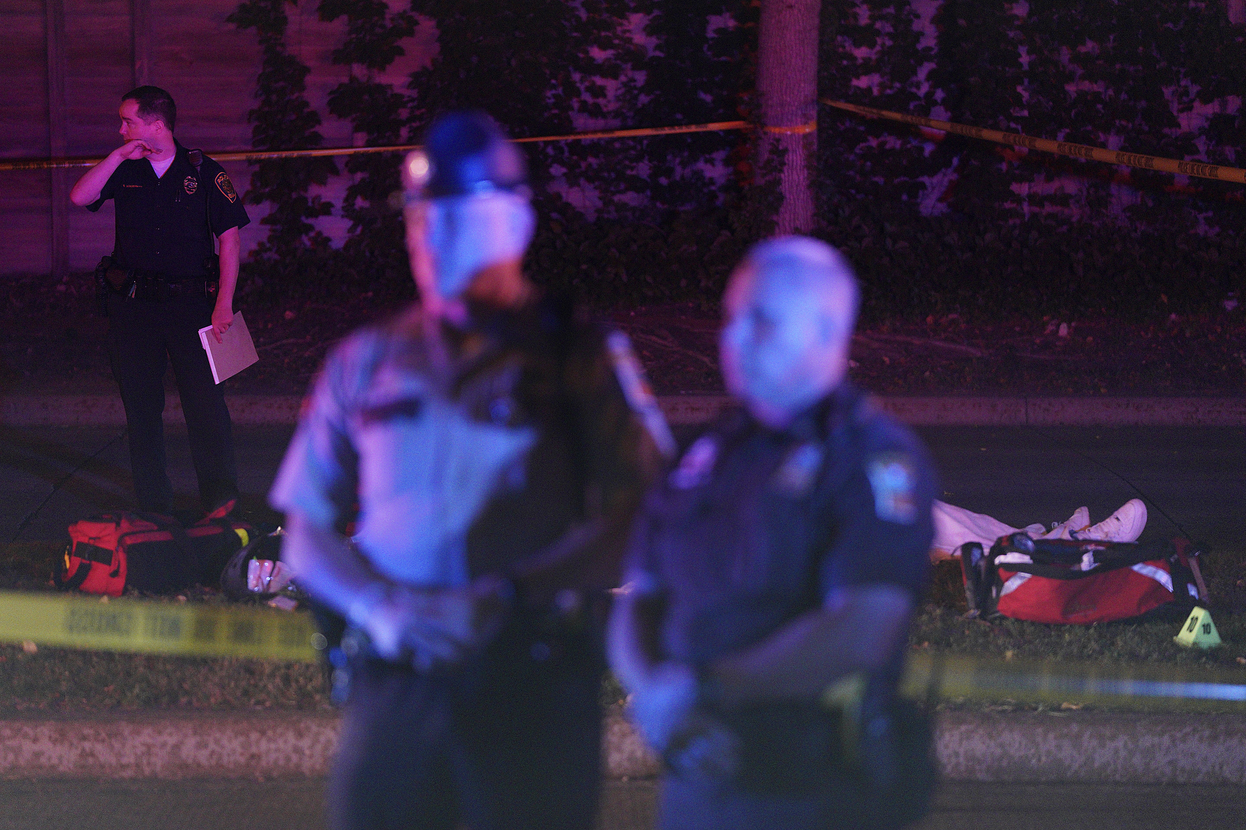 Police stand in front of a body at the scene of an officer involved shooting on East 77th Street in Richfield, Minn., Saturday night, Sept. 7, 2019. Police near Minneapolis shot and killed a driver following a chase after he apparently emerged from his car holding a knife and refused their commands to drop it. The chase started late Saturday night in Edina and ended in Richfield with officers shooting the man, Brian J. Quinones, who had streamed himself live on Facebook during the chase. (Anthony Souffle/Star Tribune via AP)