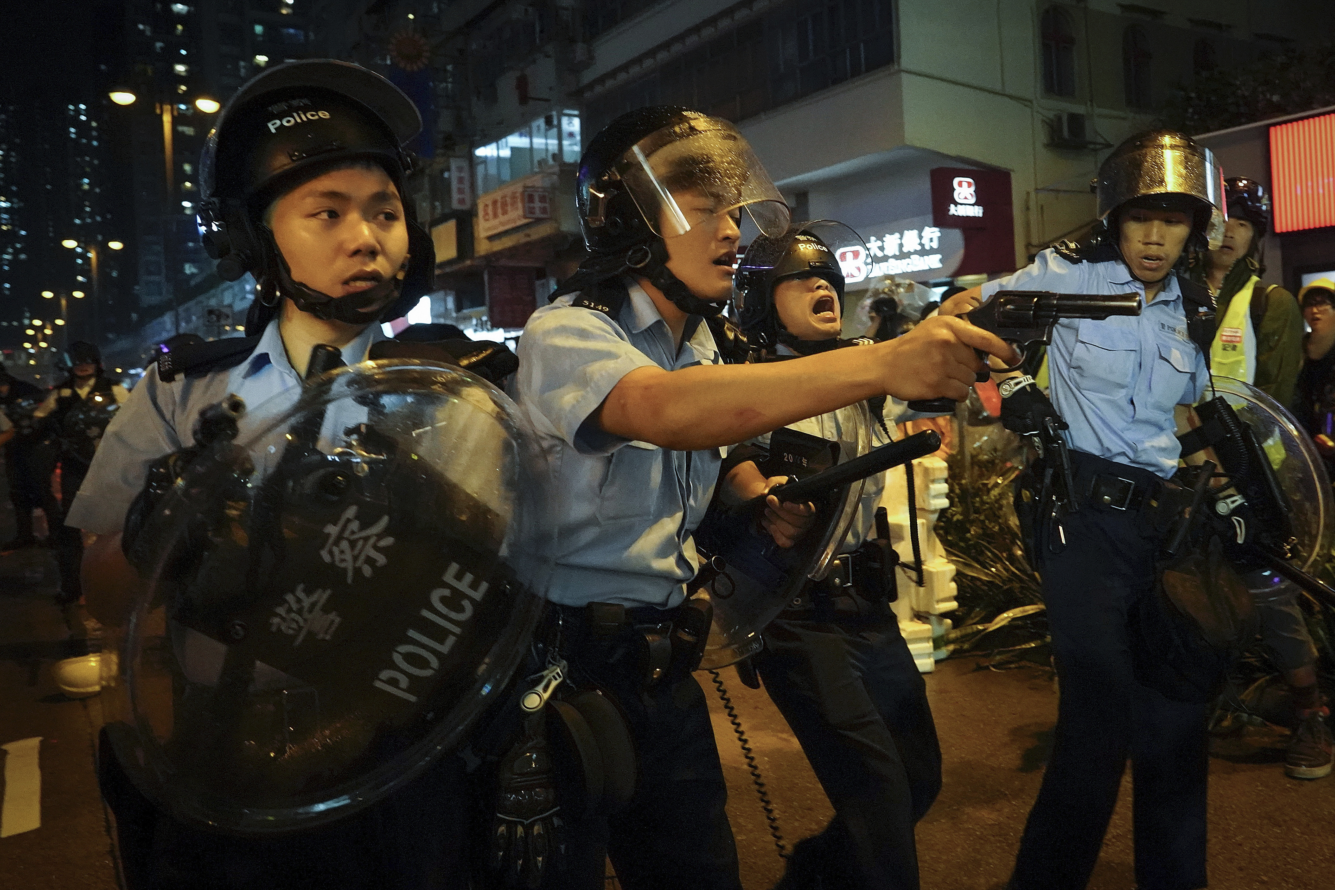 The Latest: Hong Kong police confirm warning shot, arrest 36