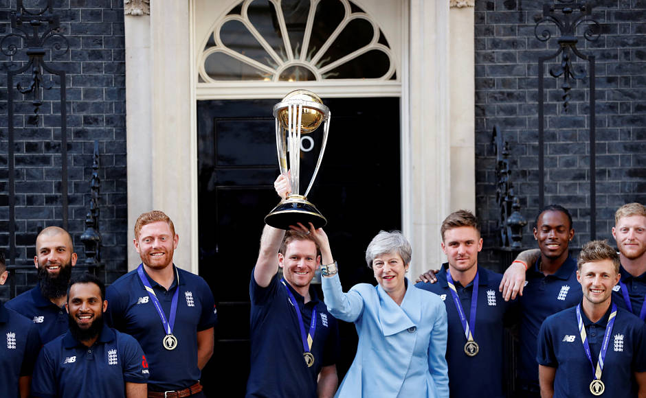 Players of England's Cricket World Cup-winning team post for a picture with Great Britain's Prime Minister Theresa May. Here, England captain Eoin Morgan and Theresa May are holding aloft the trophy. Reuters