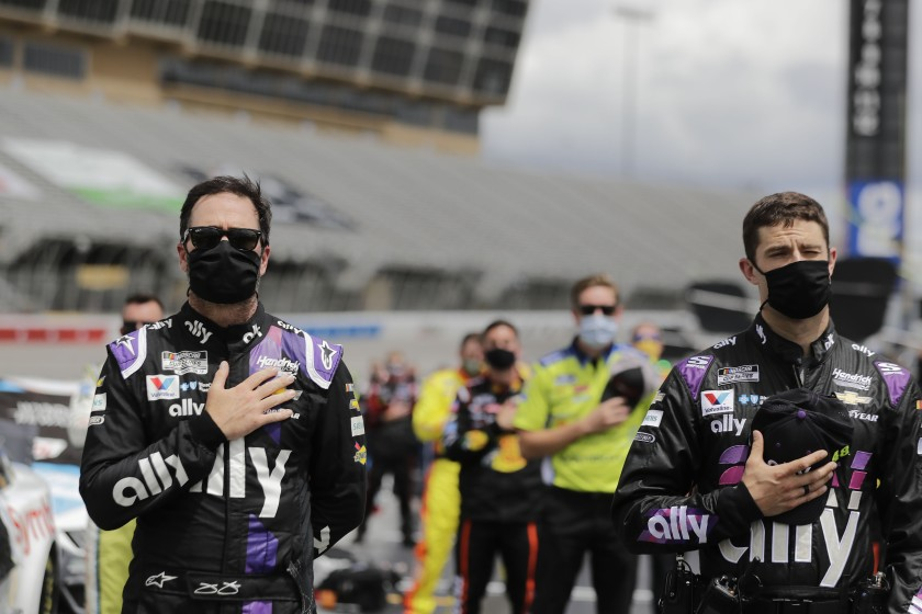 """Jimmie Johnson stands with crew members during the national anthem Sunday at Atlanta Motor Speedway. <span class=""""copyright"""">(Brynn Anderson / Associated Press)</span>"""